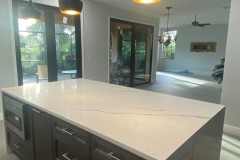 Kitchen island with marble waterfall countertops and built in microwave oven