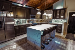 Condominium kitchen renovation with kitchen island, dark cabinets, and high ceiling