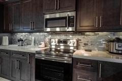 Dark wood cabinets, glass backsplash, stainless steel appliance kitchen remodeling in Deerfield Beach