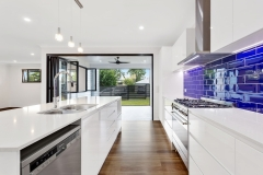 Modern white kitchen with bold blue backsplash remodeled in Fort Lauderdale