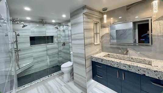 Bathroom renovation in Coral Springs with custom tilework, walk in dual shower, and blue vanity