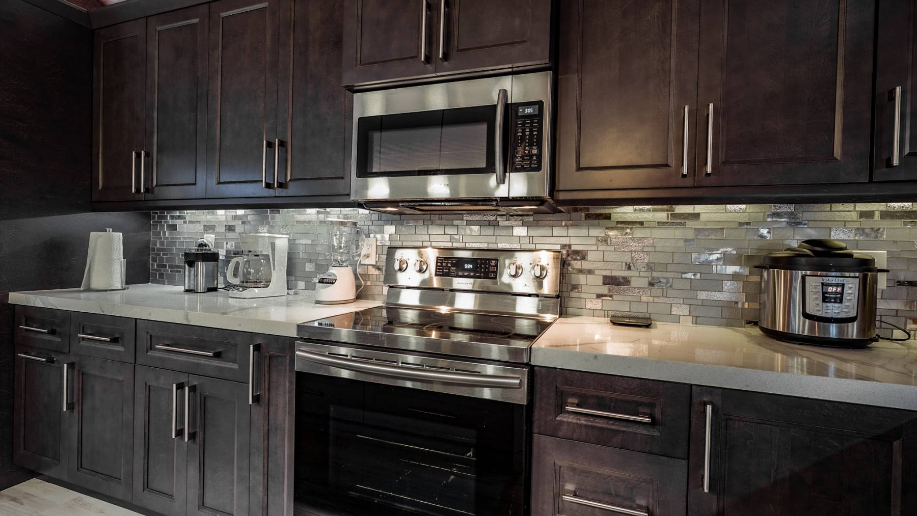 Sophisticated dark cabinetry in kitchen renovation Deerfield Beach home