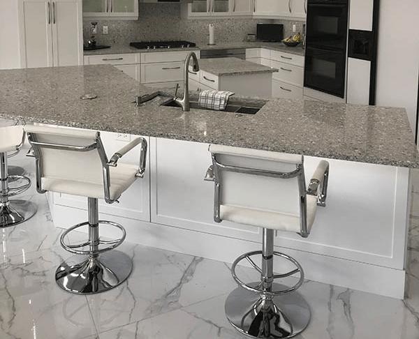 Kitchen island in Tamarac, FL home with white bar seating and granite countertops